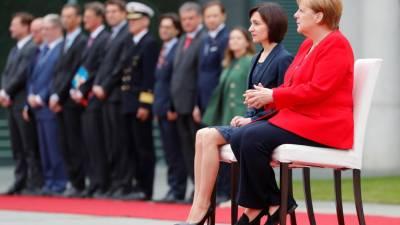 Merkel volta a sentar-se durante honras militares